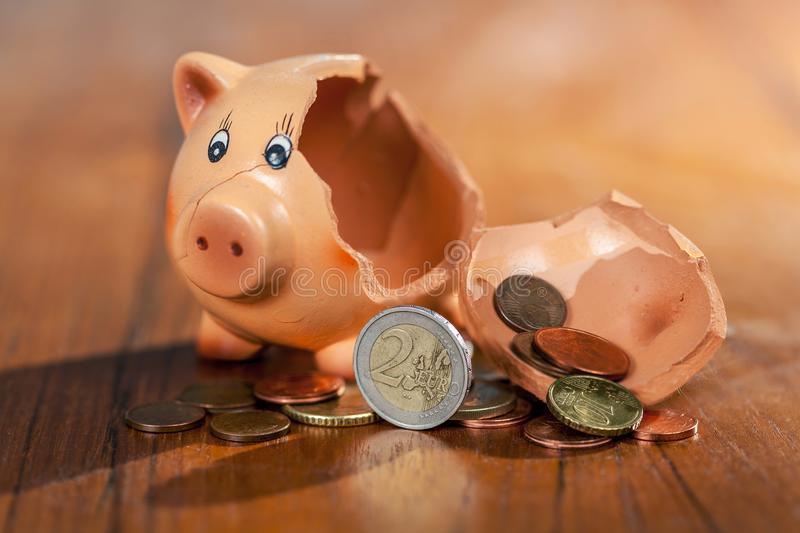 Broken piggy bank and euro coins royalty free stock image