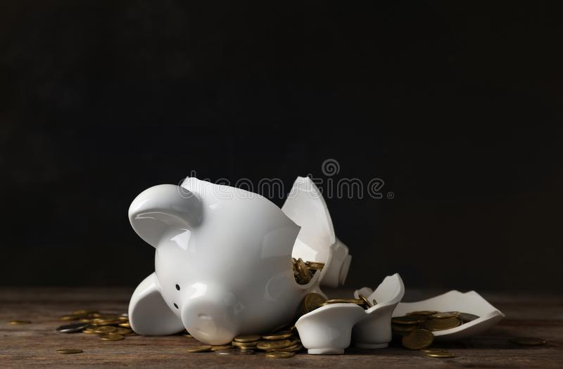 Broken piggy bank with money on table. Against dark background royalty free stock image