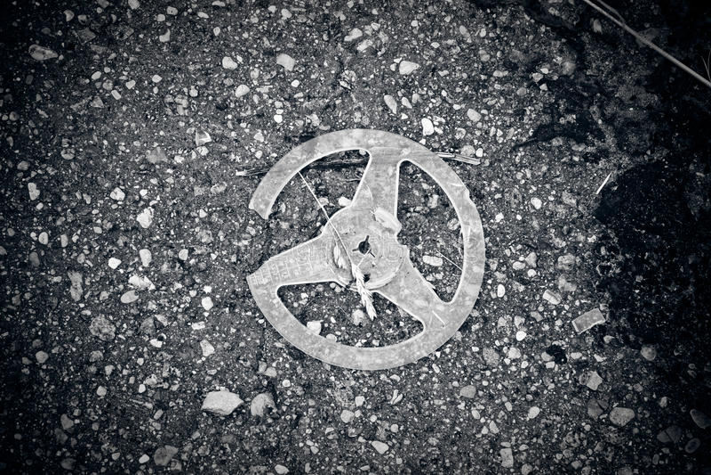 Broken plastic reel on asphalt stock image