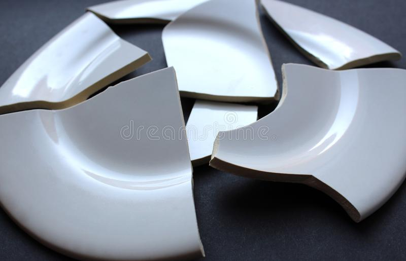 A broken white porcelain dish that does not stick together. Broken, plate, white, background, porcelain, isolated, plates, dishware, metaphor, accident, quarrel royalty free stock photography