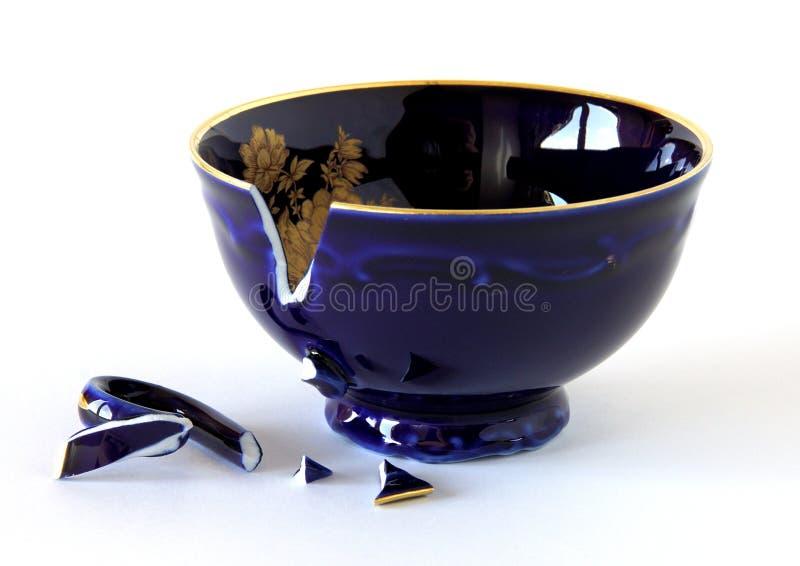 Broken porcelain cup. Broken porcelain cobalt blue cup on white stock photos