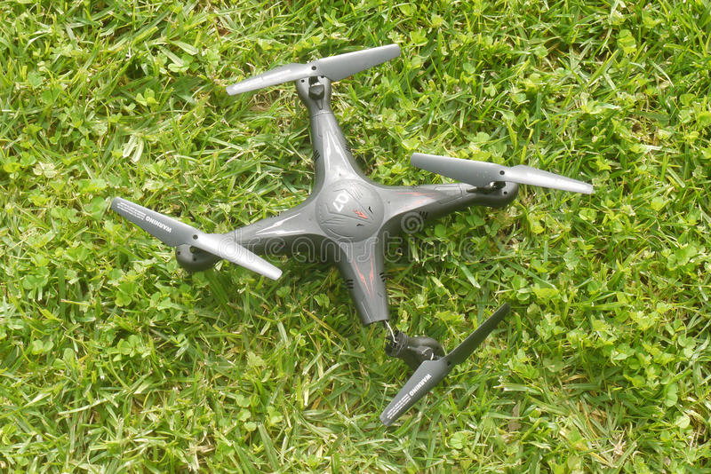 Broken quadcopter on grass stock photography
