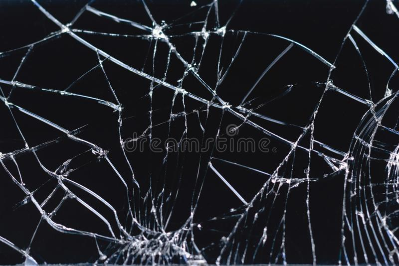 Broken and racked glass screen smartphone , white lines on black background,   design element, backdrop texture stock photography
