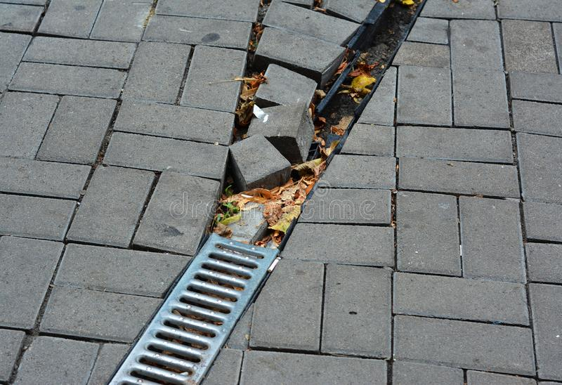 Broken rain gutter downspout pipe for roof runoff with damaged open water drainage in the pavement to repair. Close up on Broken rain gutter downspout pipe for royalty free stock images