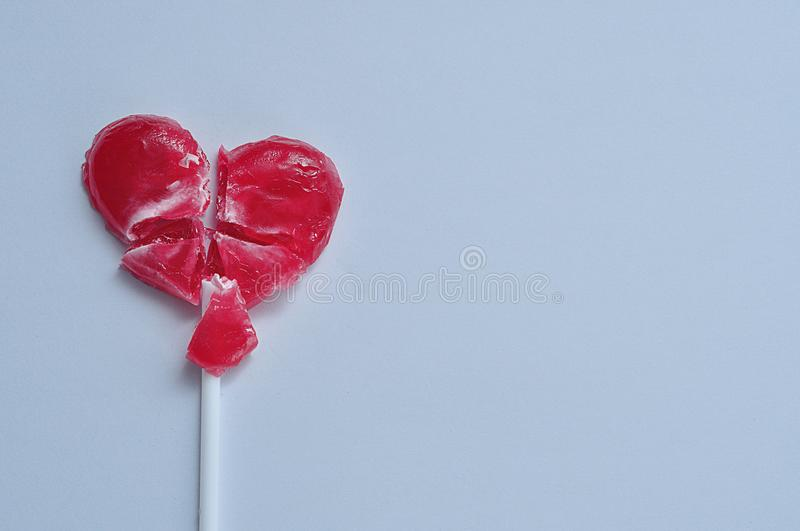A broken red heart lollipop symbolizing a broken heart royalty free stock image