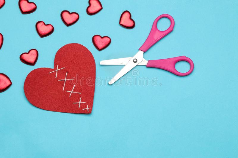 Broken red heart and small hearts with scissors on a bright blue background. view from above royalty free stock photo