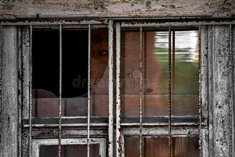 Broken rusty window with metal grating. Is close stock photography