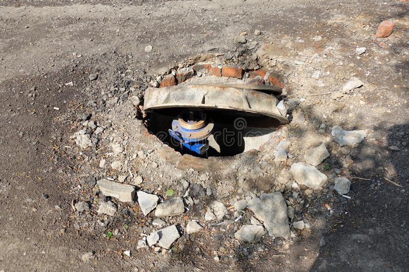 Broken sewer on the road. Danger of injury. Repair of communications.  stock image
