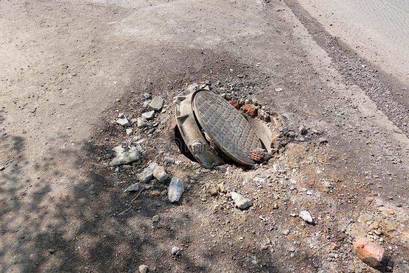 Broken sewer on the road. Danger of injury. Repair of communications.  stock photos
