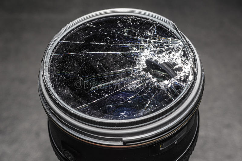 Broken & Shattered Filter on a lens. Close up of a Broken & Shattered Filter on a lens on a black background royalty free stock photo
