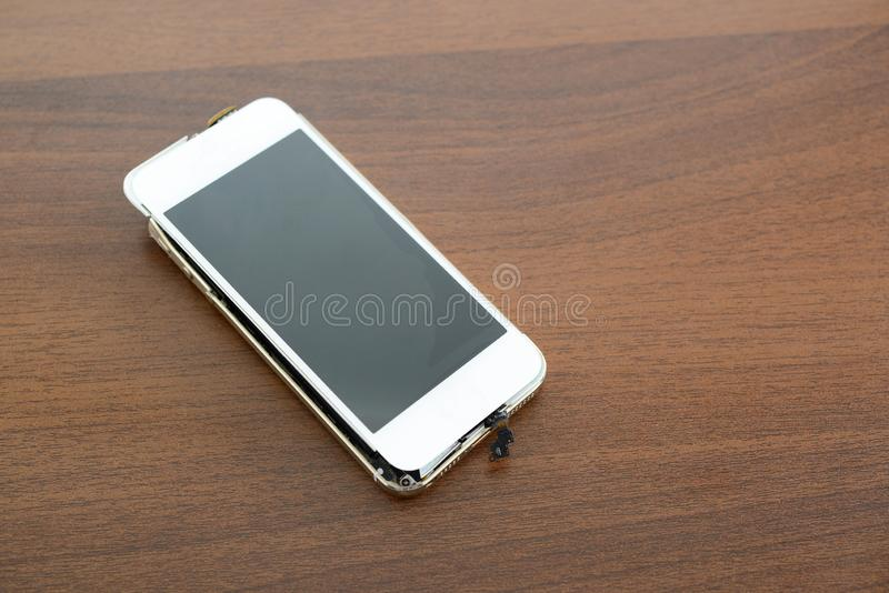 Broken smart phone. On the desk stock photos
