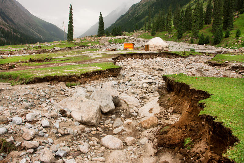 Broken soil by earthquake and lonely dwelling of a farmer of Central Asia. Near the mountain forest stock photo