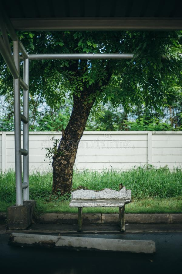 Broken stone bench with metal lamp post and big green tree and w stock photos