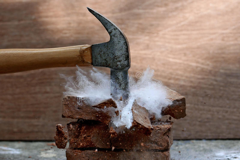 Broken stone. Smashing a stone with a hammer stock photography