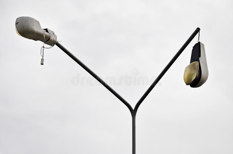 Broken street lamp. Detail shot with a broken street lamp with overcast sky on background stock images