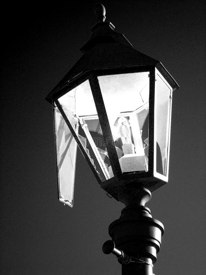 Broken street lamp. Broken hooligans street lamp in black and white. Streetlight as a symbol of vandalism. Dark colors give a gloomy, mournful mood and mystery royalty free stock image