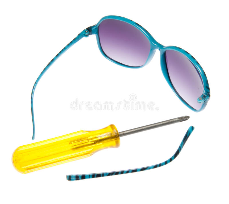 Broken Sunglasses. Broken blue sunglasses with purple lenses and a yellow screwdriver to fix them. Studio isolated on white with a clipping path royalty free stock image
