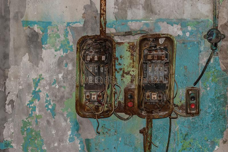 Broken switches on the wall. Broken switches in the workshop of abandoned factory stock photo