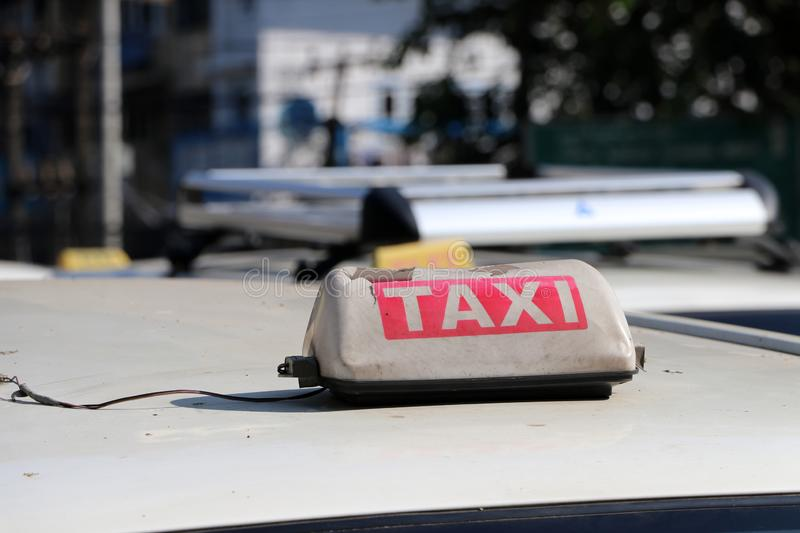 Broken taxi light sign or cab sign in drab white and red color with white text on the car roof at the street royalty free stock images