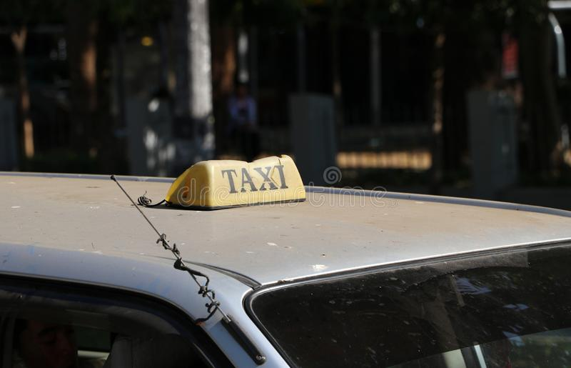 Broken taxi light sign or cab sign in drab yellow color with black text on the car roof at the street blurred background royalty free stock photos