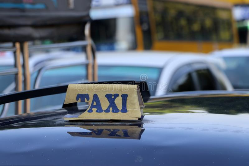 Broken taxi light sign or cab sign in drab yellow color with blue text on the car roof royalty free stock photos