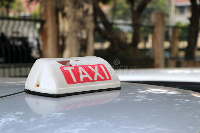 Broken Taxi light sign or cab sign in white and red color with white text on the car roof at the street blurred background stock photos