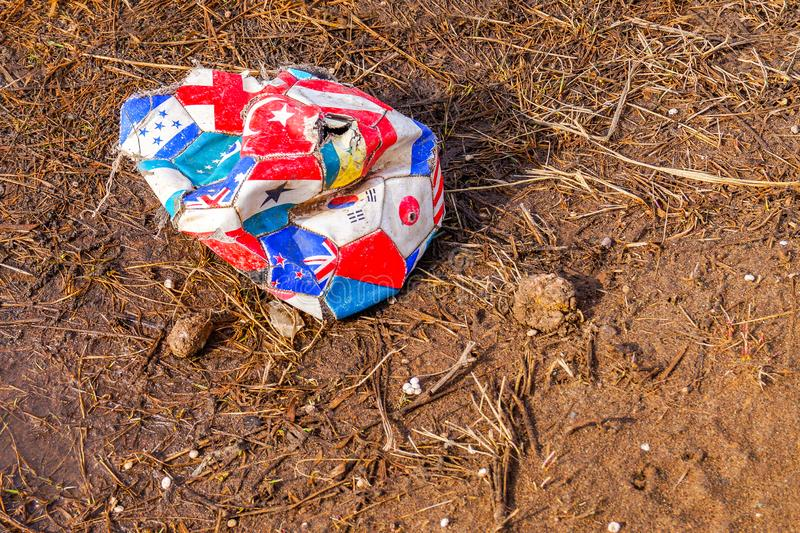 A broken and thrown old soccer ball lies on the ground. Sports equipment stock photography