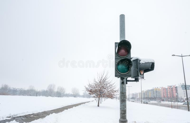 Broken and out of use traffic light on the urban street cross walk for pedestrians in the city damaged by snow in the winter time stock image