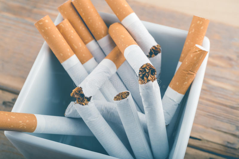 Broken unsmoked cigarettes in a white ashtray. Quit Smoking - Broken unsmoked cigarettes in a white ashtray with blueish filter royalty free stock image