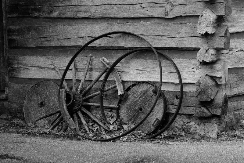 Broken wagon wheel against a log cabin royalty free stock photo