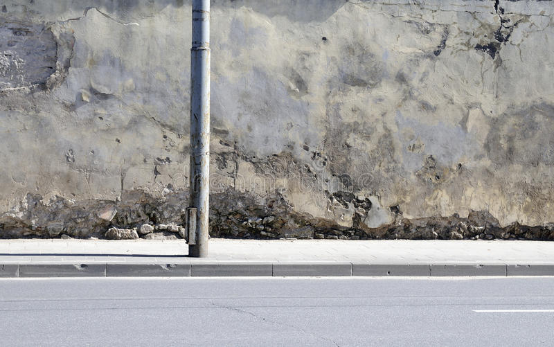 The broken wall near to road stock photos