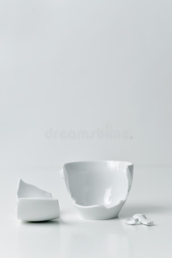 Broken white ceramic coffe cup. A broken white ceramic coffe cup with its pieces spread out on a white table, against a white background with a blank space on royalty free stock image