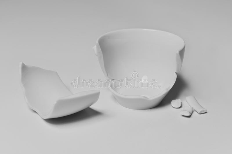 Broken white ceramic coffee cup. A broken white ceramic coffee cup with its pieces spread out on a white table, against a white background stock images