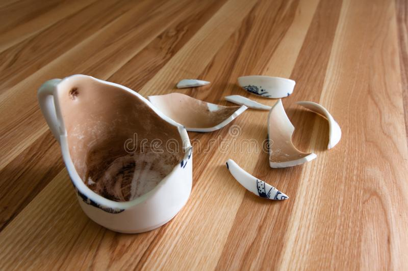 Broken white Cup with shards on a wood background stock photography
