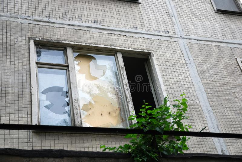 Broken window glass in abandoned house clogged with plywood. Broken window in abandoned house clogged with plywood, tree growth on windowsill royalty free stock image