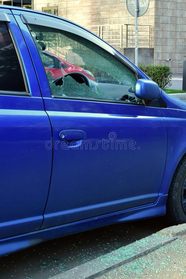Broken window from driver`s side. Attempt to steal bluecar. splinters of glass on asphalt royalty free stock photo