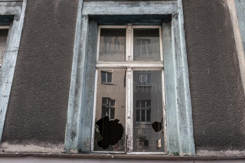 Broken window glass in abandoned old building. Dirty facade. Destruction concept. Vandalism concept. Grunge architecture exterior. Broken window with royalty free stock images