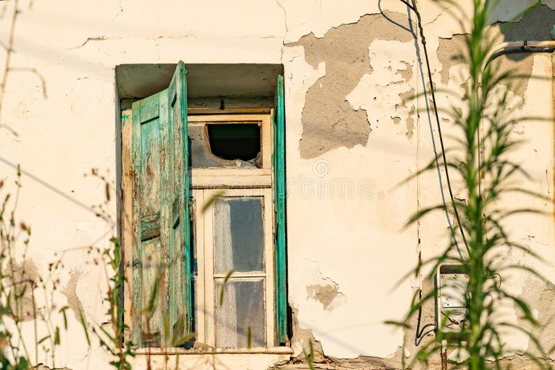 Broken window in old rustic wall with green shutter. And deteriorating wall while the weds grow around royalty free stock photos