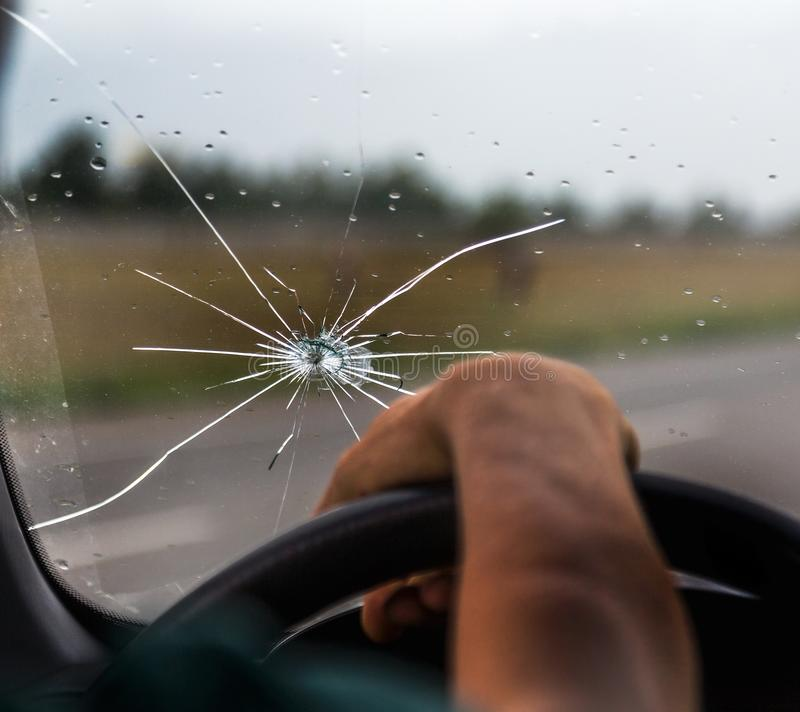 Broken windshield of a car. A web of radial splits, cracks on the triplex windshield. Broken car windshield, damaged glass with stock photography
