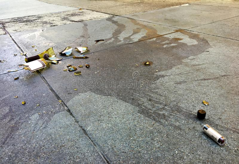 Broken wine bottle and lipstick on concrete pavement in the city stock photo