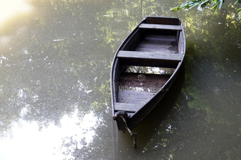 Broken wooden boat still afloat on a river. Broken wooden boat still afloat on a river with sunlight stock photography