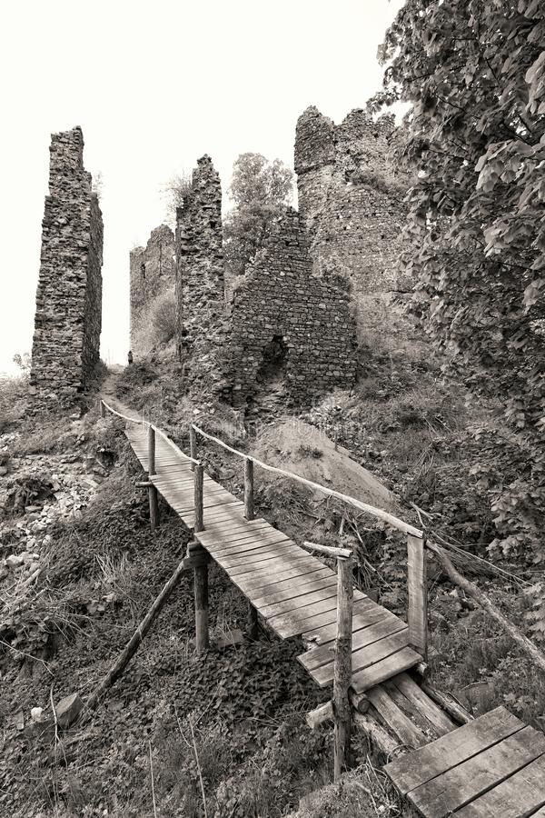 Broken wooden bridge by the old castle remains royalty free stock image
