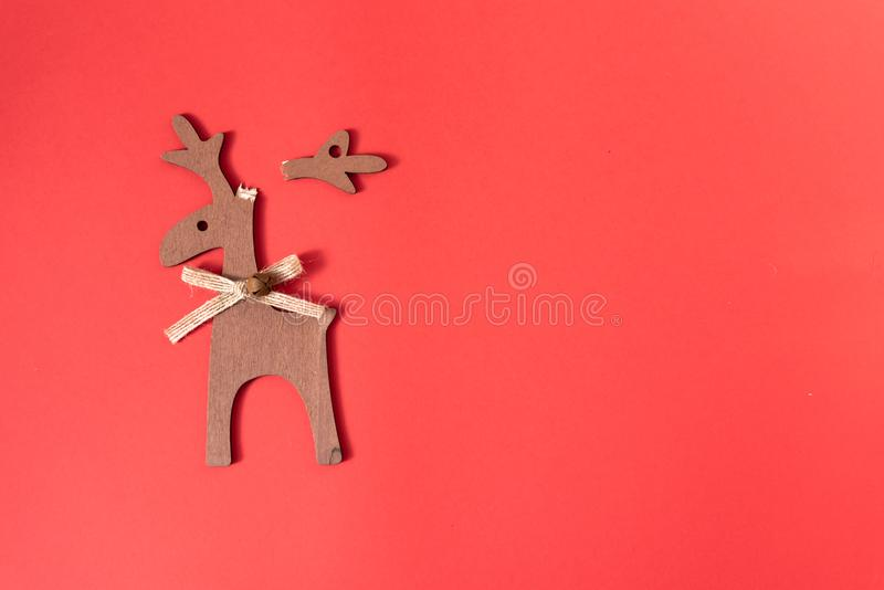 Broken wooden deer decoration on red background. Christmas and New Year decoration. Repair and recovery concept. Top view, copy stock images