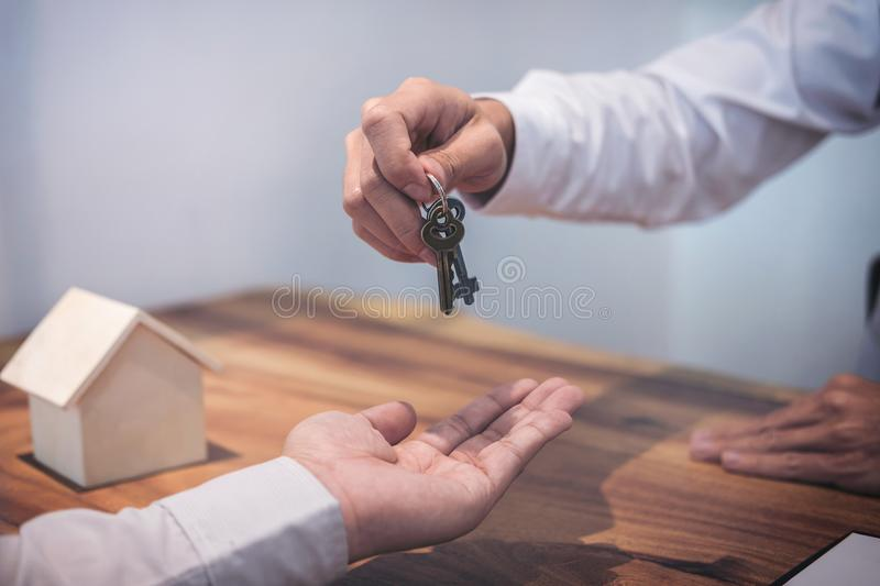 Broker agent`s hand holding House key in insurance, giving to bu. Yer customer, real estate agent royalty free stock images