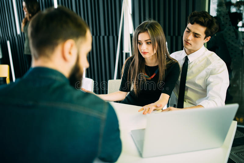 Broker making a presentation to a young couple showing them a document which they are viewing with serious expressions stock images