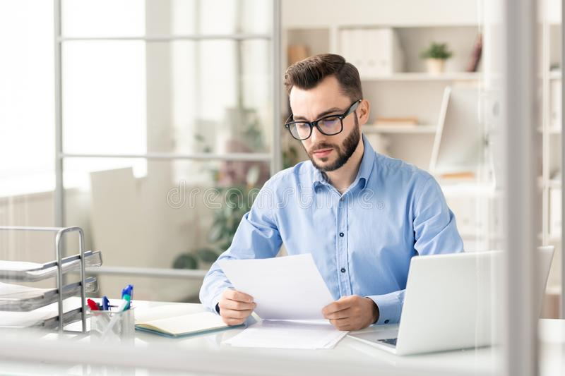 Broker in office. Serious financier in smart casual reading financial documents by desk while preparing papers for deal royalty free stock photos