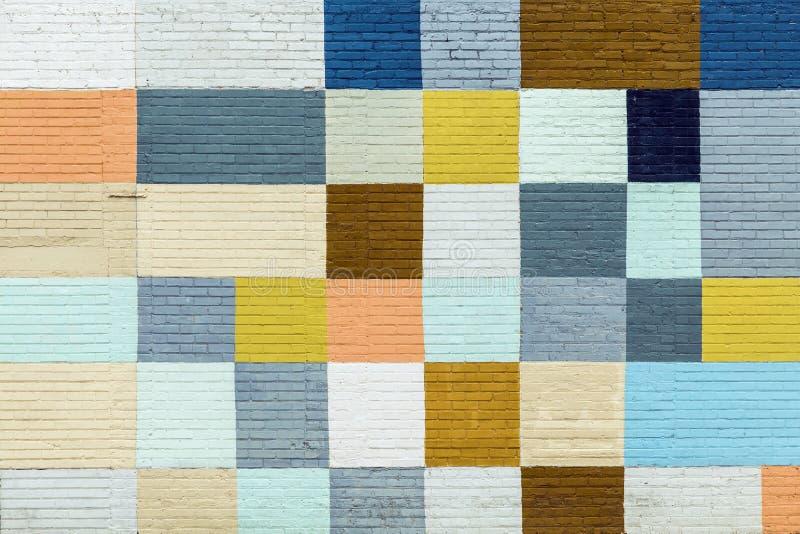 Brokiga fyrkanter som målas på en tegelstenvägg arkivbilder