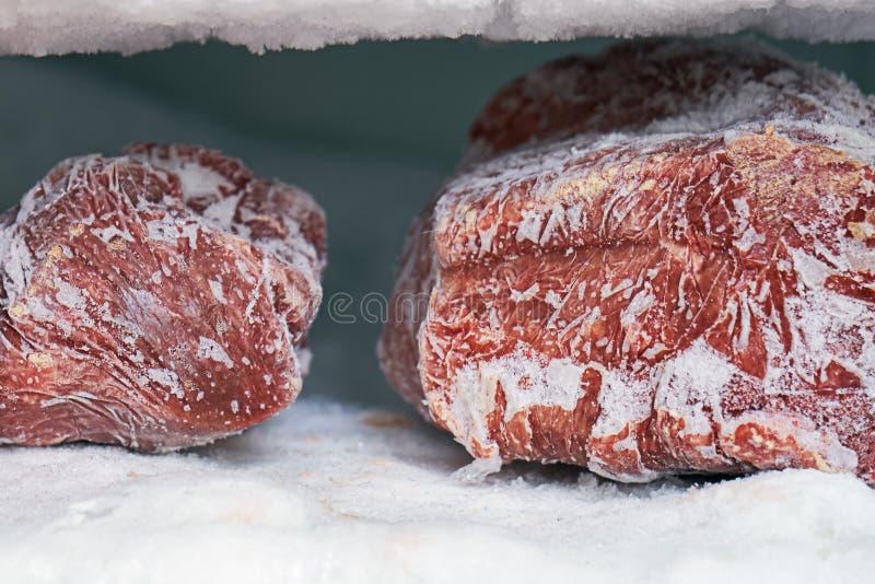 Brokken van rood vlees in een diepvriezer met een grote hoeveelheid bevroren ijs en sneeuw stock afbeelding