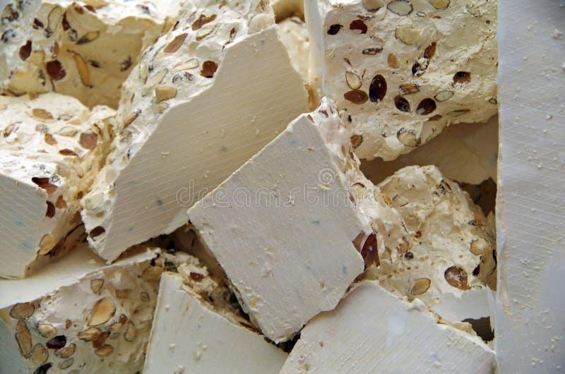 Brokken van witte torrone met amandelen stock afbeelding