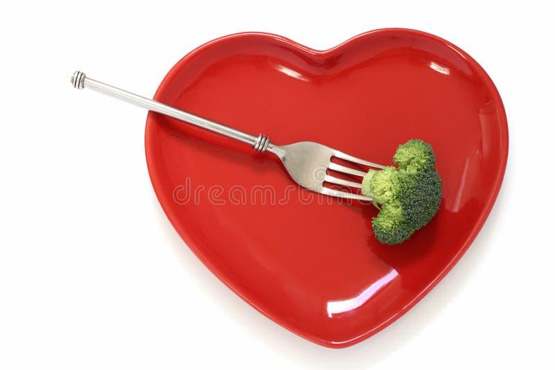 Brokkoli auf einer Gabel und roten einer Innerformplatte stockbilder